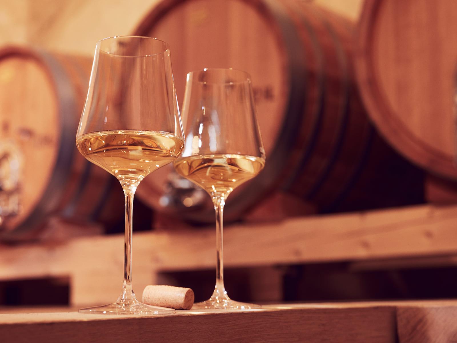 Zwei Weingläser vor Weinfässern
